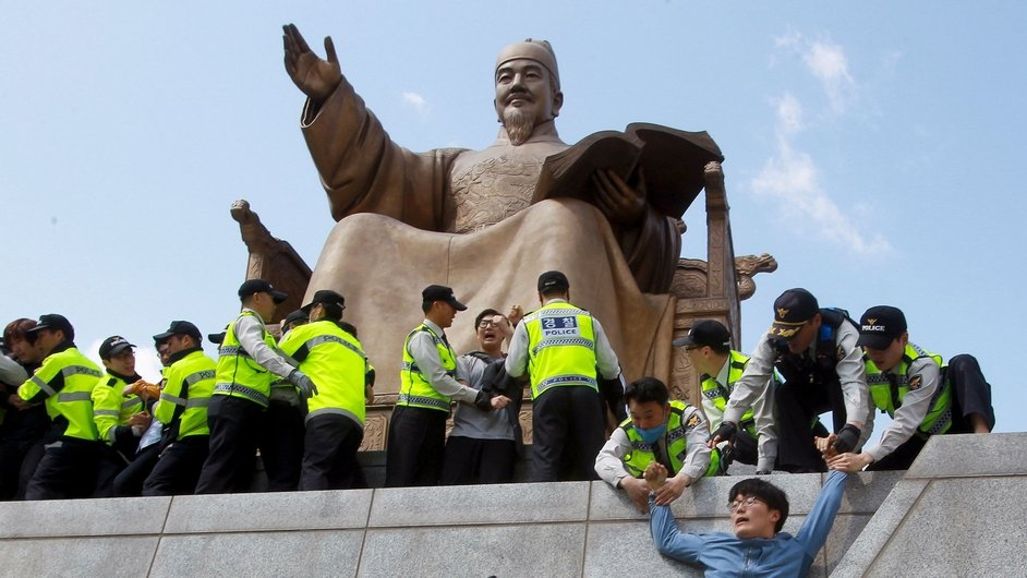 South Korean policemen detain university student protesters during a rally against the government in Seoul
