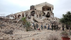 Syrian government forces sift through the rubble following the explosion