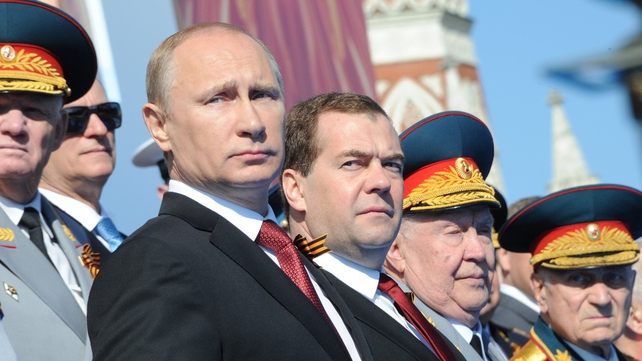 Vladimir Putin and Russian Prime Minister Dmitry Medvedev with veteran military figures as they watch the parade