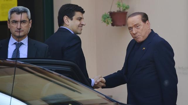 Silvio Berlusconi (R) arrives at the Catholic hospice 'Sacra Famiglia'
