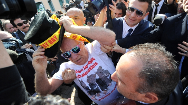 Berlusconi was heckled by a trade unionist in a clown hat