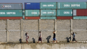 Construction workers pass a container yard at a port in Yangon