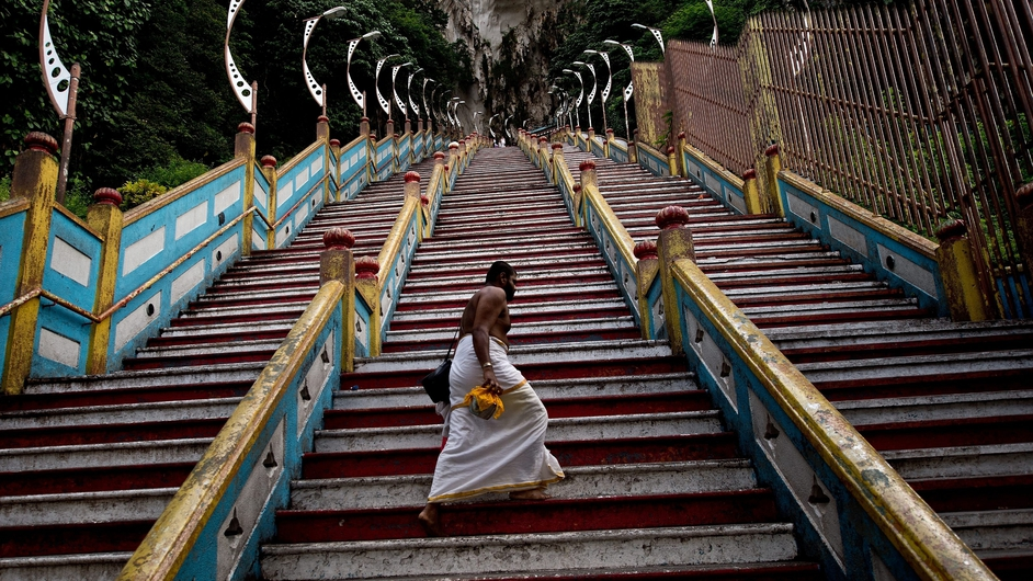 A Hindu priest walks up the 272 stairs to the Batu Caves temple outside of Kuala Lumpur
