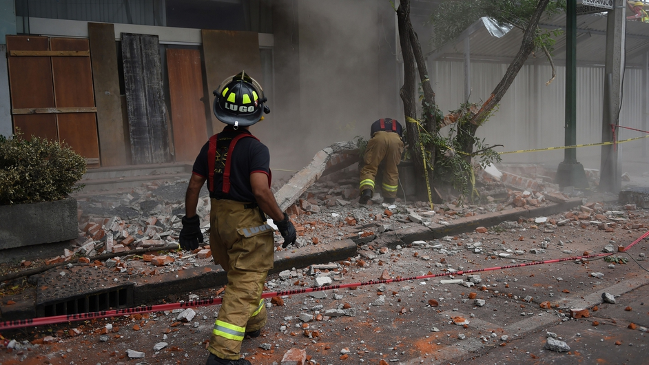 Firefighters work to demolish a damaged wall after a strong earthquake in Mexico City
