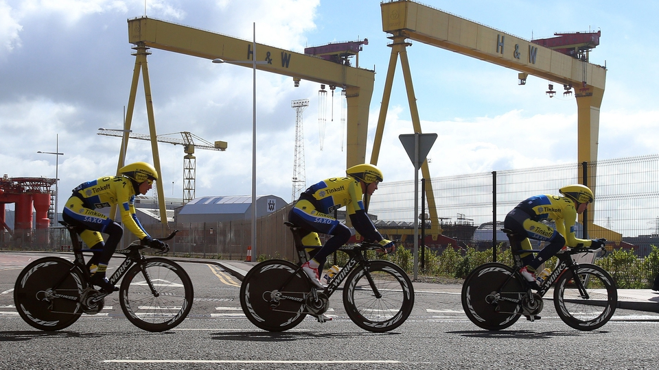 Members of the Tinkoff-Saxo team pass the Harland and Wolff cranes Samson and Goliath during a training session on Friday