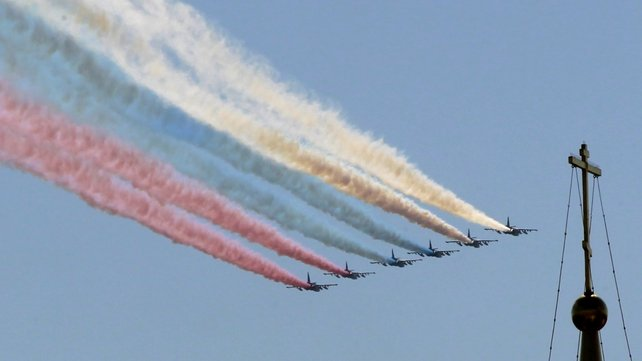 Russian Air Force fighter planes release coloured smoke during a military parade