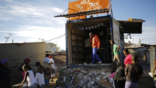 A shop owner cleans up after overnight violence in the Alexandra township