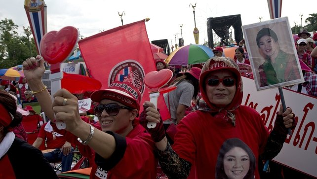 Thai pro-government 'Red Shirts' protesters hold portraits of ousted Thai prime minister Yingluck Shinawatra as they rally in Bangkok