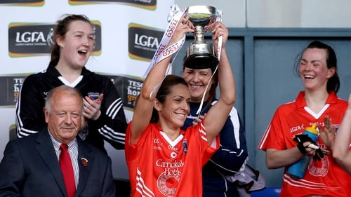 Caitlin Malone lifts the trophy after the game