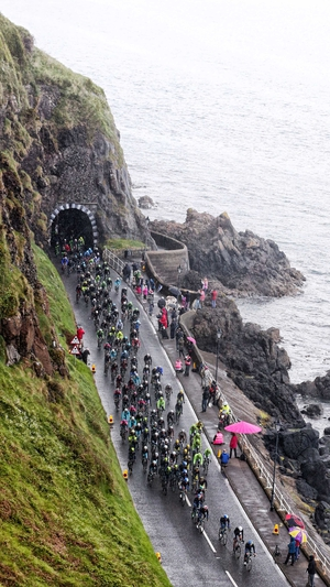 The Giro d'Italia Peloton makes its way along the County Antrim coast road at Drains Bay, Larne