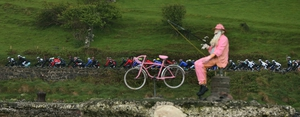 The Peloton travels along the North Antrim Coast on Saturday, watched by a giant cyclist who is doing some fishing