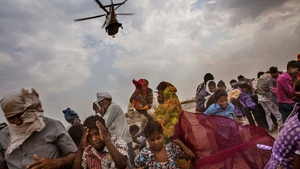 Supporters of BJP leader Narendra Modi run as a helicopter carrying Modi takes off after a rally in India