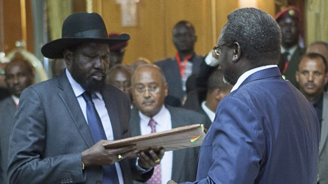 Salva Kiir (L), President of South Sudan, and Riek Machar (R), SPLM Opposition leader, hand over the Cessation of Hostilities treaty