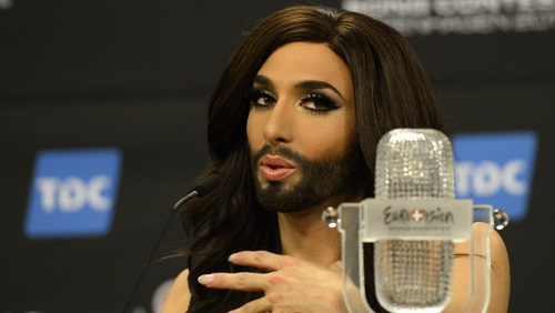 Conchita Wurst representing Austria poses with the trophy at a press conference after winning the Eurovision