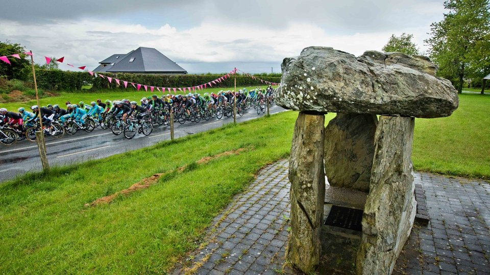 The Giro peloton passes by the Monasterboice dolmen on Sunday