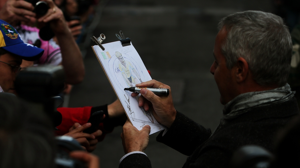 Stephen Roche signs a sketch of his son Nicolas at the finish line in Dublin on Sunday