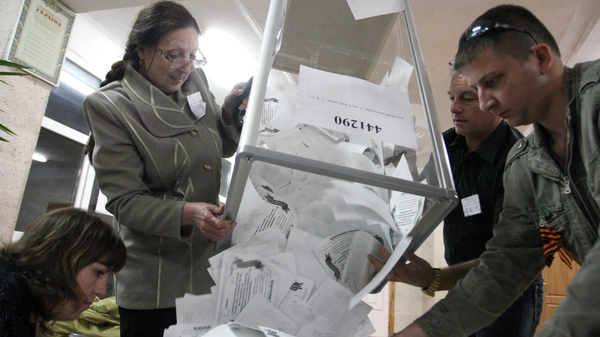 Members of a local election commission empty ballot boxes in Luhansk in eastern Ukraine