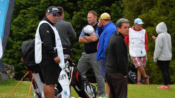 Alastair Forsyth of Scotland (centre), talks to fellow golfers after his caddie Ian McGregor tragically died