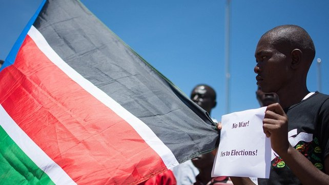 A South Sudanese man holds a placard reading 'No to War, Yes to Elections!' and the country's flag