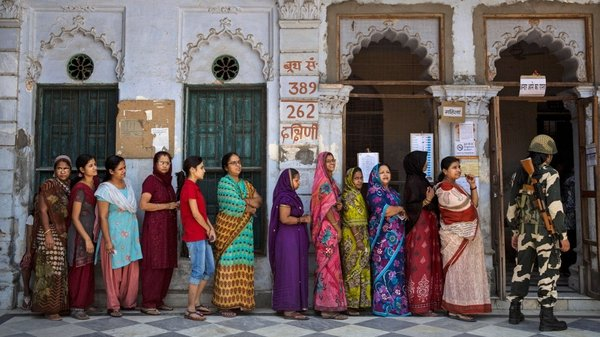 A border police officer stands guard as Indians wait in line to vote at a polling station in Varanasi