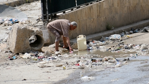A man collects stagnant murky water from the side of a road in a rebel-held area in Aleppo