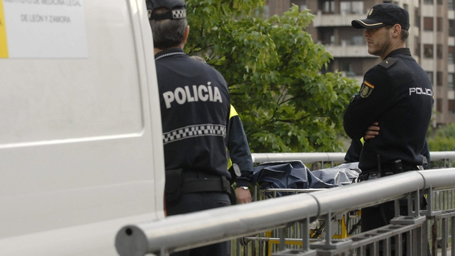 Two policemen stand next to the body of Isabel Carrasco after the shooting in northern Spain