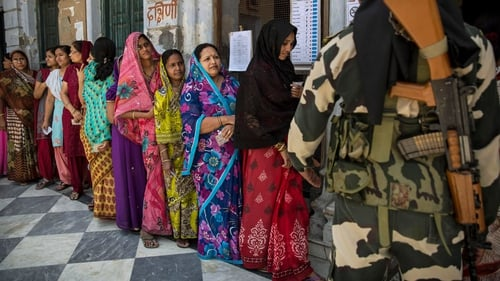 Indian women wait in line to vote as a border police officer stands guard at a polling station in Varanasi, India.