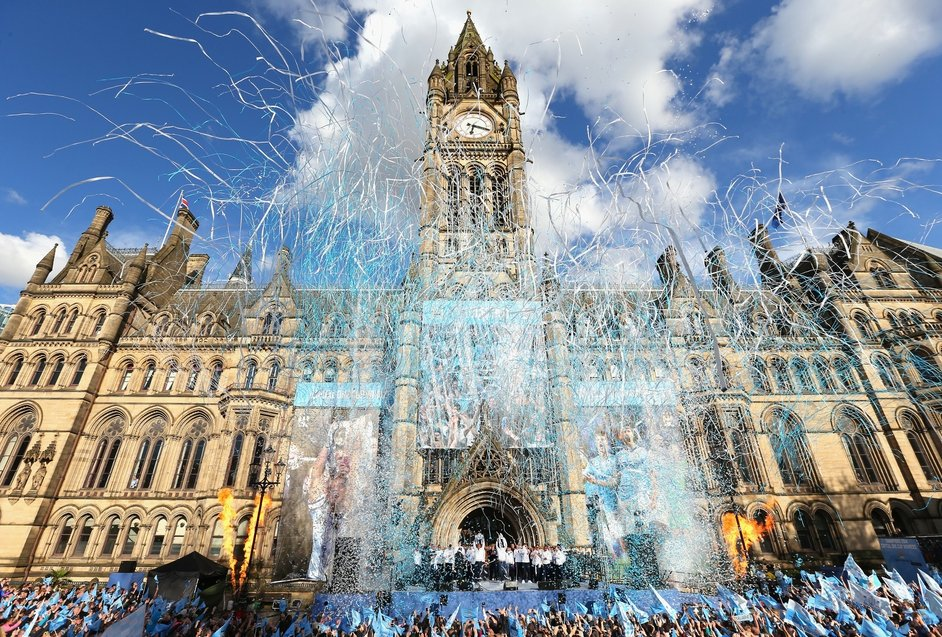 Manchester City's Vincent Kompany lifts the Barclays Premier League Trophy aloft outside Manchester Town Hall on his team's victory parade through the city.