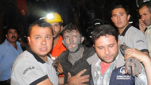 Miners assist an injured colleague after the mine explosion in Manisa
