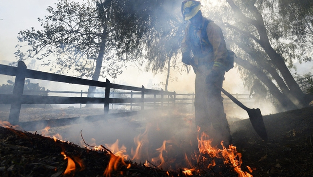 A firefighter puts out flames near the Rancho Santa Fe neighbourhood north of San Diego, California