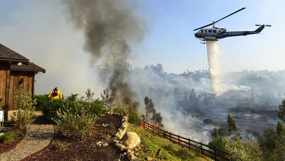 A helicopter dumps water on a farm as wildfires threaten San Diego in Califonia
