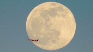 A jetliner passes in front of a full moon as it takes off from San Francisco International Airport