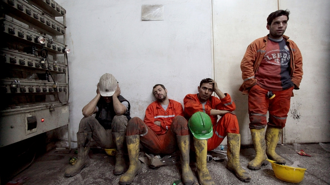 Exhausted miners rest as they await their trapped friends