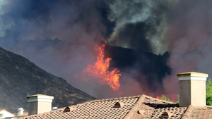 Flames flare up on a hillside behind an apartment complex near California State University