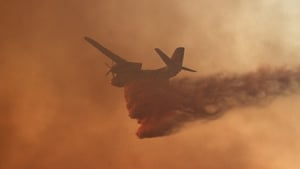 An airplane drops fire retardant on a fire in the San Marcos area