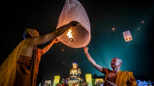 Buddhist monks release a lantern into the air at Borobudur temple during celebrations for Vesak Day in Java