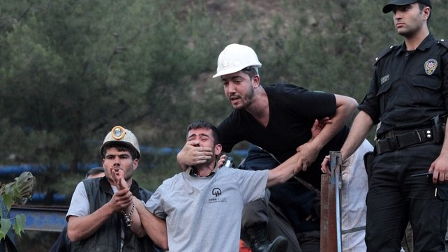 A relative of one of the missing men is restrained outside the mine