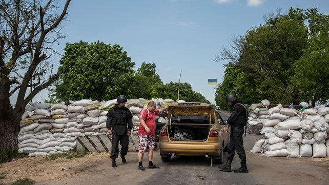 Ukrainian soldiers check a car at a checkpoint not far from Slaviansk, Ukraine