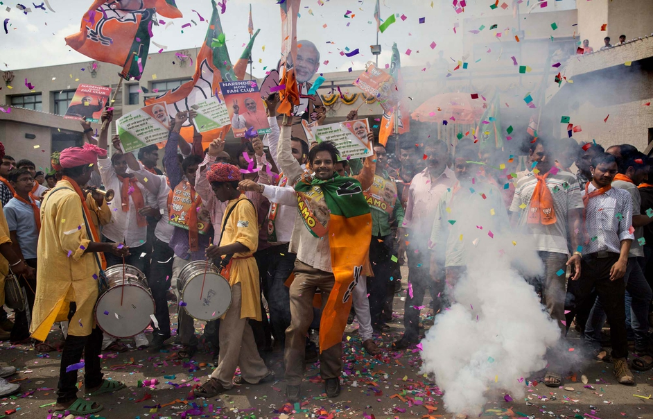 Supporters dance and set off crackers as poll results come in at the Bharatiya Janata Party's headquarters at Ahmedabad, India