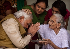 Incoming Indian Prime Minister Narendra Modi (L) is blessed by his mother Heeraben Modi on her front porch