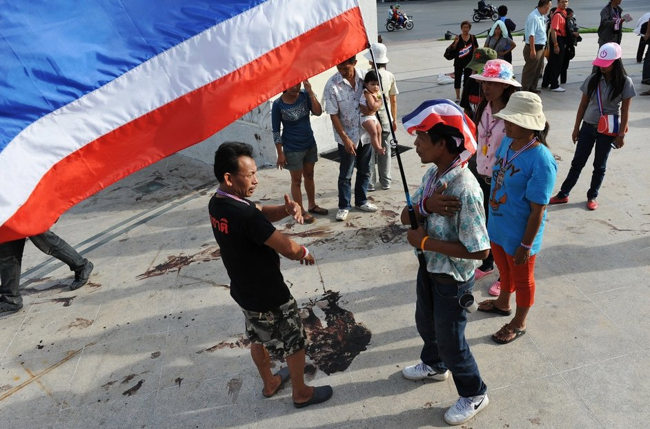 Protesters and bystanders gather at the scene of a deadly drive-by attack on an anti-government rally site at the landmark Democracy Monument in Bangkok