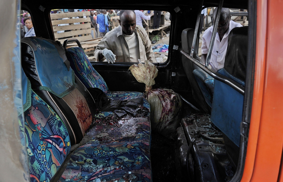 Police investigators look into a damaged public transport vehicle at the scene of the explosion