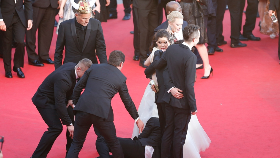 An unidentified man peeks under the dress of actress America Ferrera  during the 67th annual Cannes Film Festival