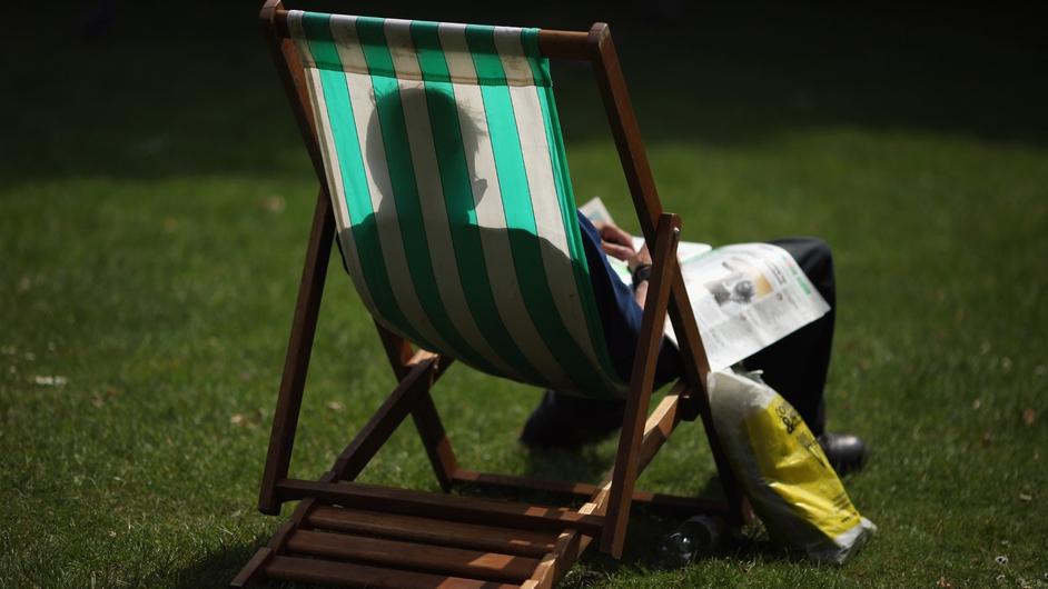 A man relaxes on a deck chair in St James's Park in London