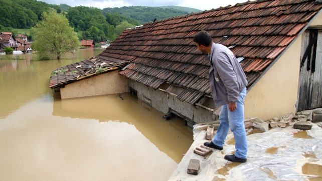 A man looks at the flooded street from the roof of a house in Pozega, 200km south-west of Belgrade, Serbia