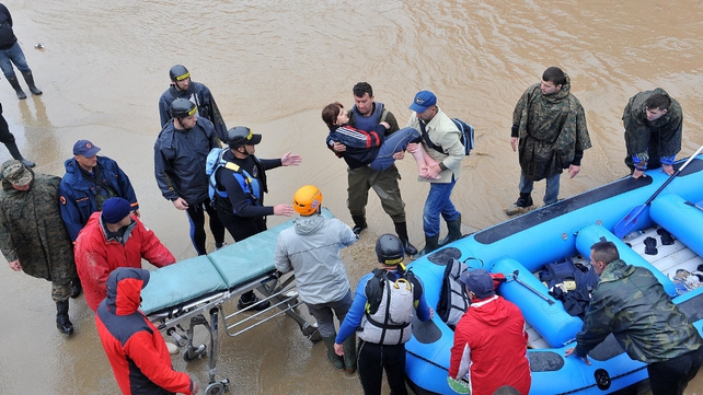 Bosnian rescuers evacuate a woman from her flooded home in the northern town of Maglaj