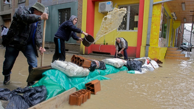 Residents try to set up a mini dam in front of their building in the town of Obrenovac, Serbia