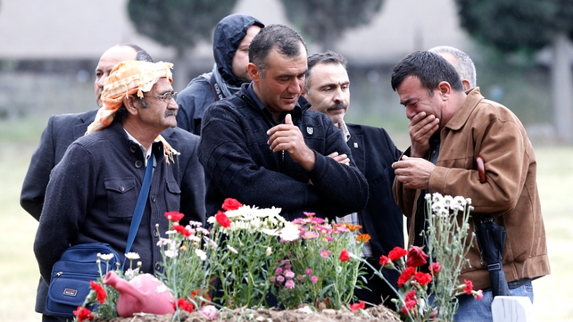 Relatives mourn next to a grave of miner killed in disaster