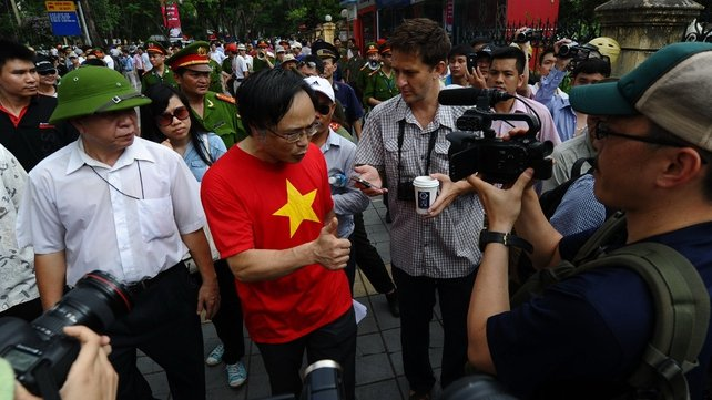 Anti-China protester Dao Minh Chau (C) speaks with reporters on a street near the Chinese embassy