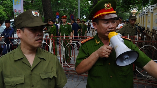 Policemen ask people to leave a street near to the Chinese embassy in Hanoi